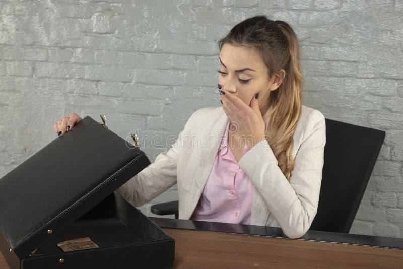Бизнес-леди удивленная содержанием портфеля стоковое изображение