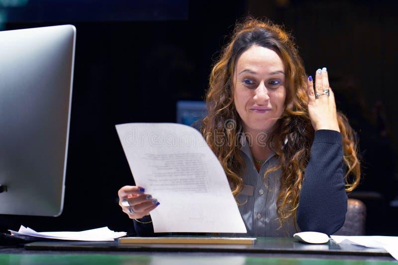 Бизнес-леди читая документ в месте для работы офиса стоковые изображения rf