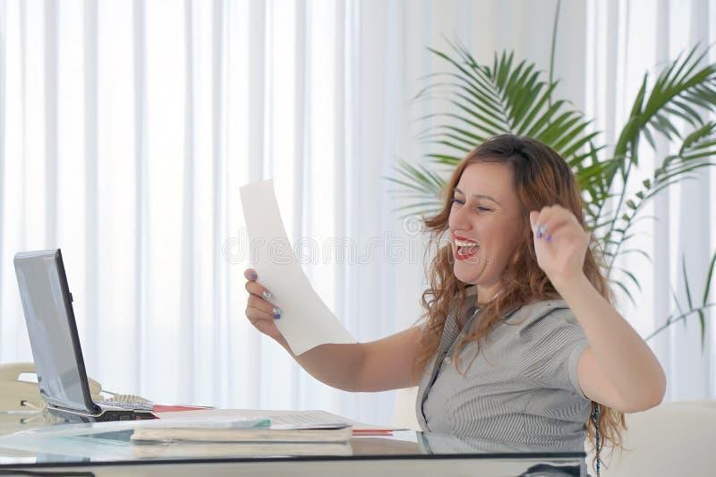 Бизнес-леди читая документ в месте для работы офиса стоковое фото