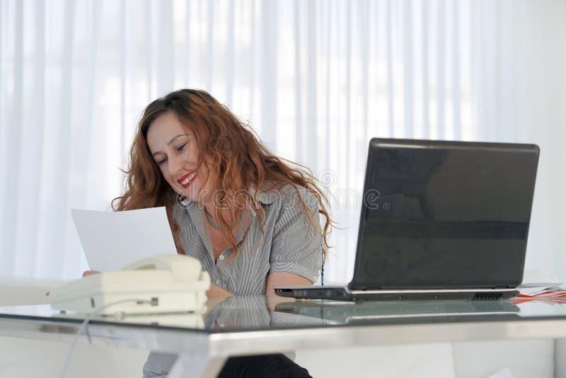 Бизнес-леди читая документ в месте для работы офиса стоковые фотографии rf