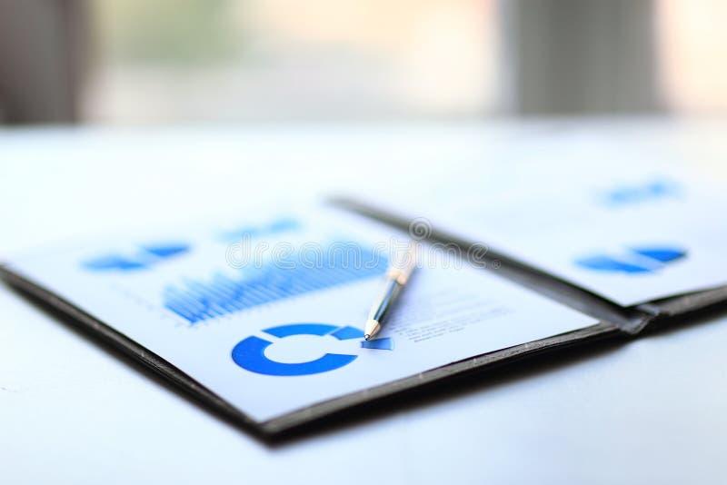 Бизнес-отчет с план-графиками финансовых и маркетинга и бизнесменом рабочего места ручки стоковая фотография rf