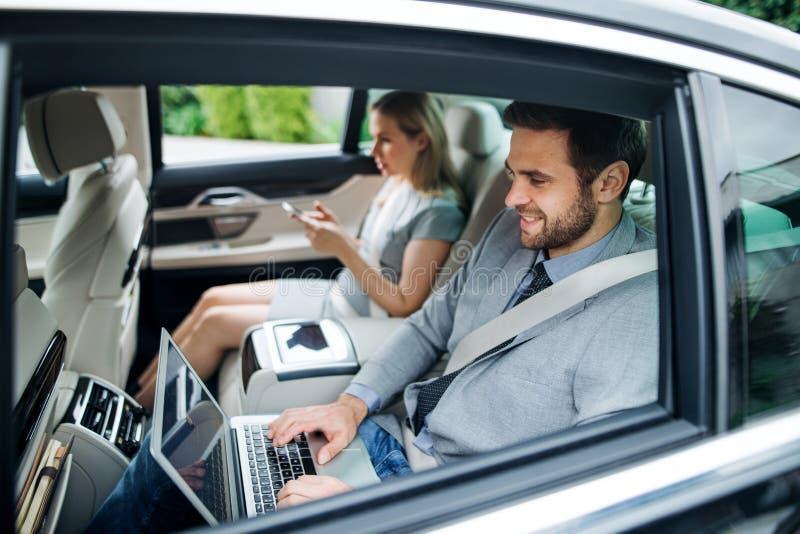 Бизнес-пара с ноутбуком, сидящим на задних сиденьях в автомобиле, работ стоковые фото