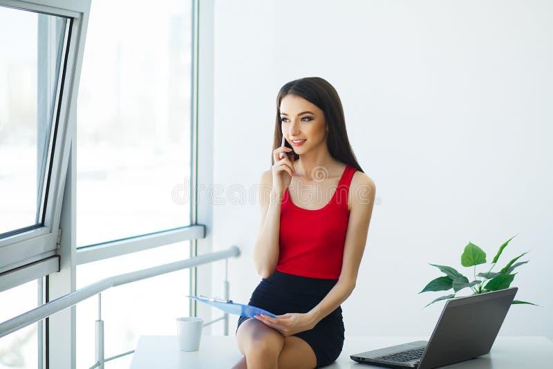 Бизнес Портрет молодой женщины держа голубую руку папки Одетый в красной футболке и черной юбке женщина дела 2 стоковые фотографии rf