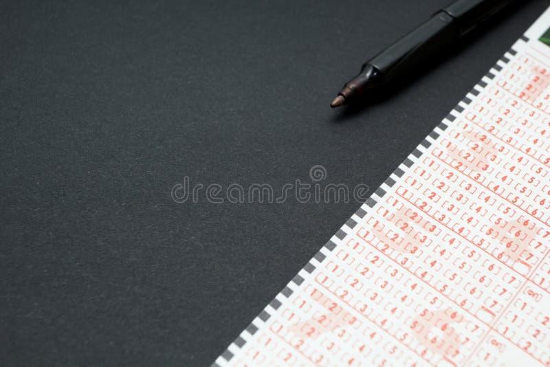 Билет лотереи с ручкой, номером маркировки человека Черная предпосылка, космос для текста стоковая фотография rf