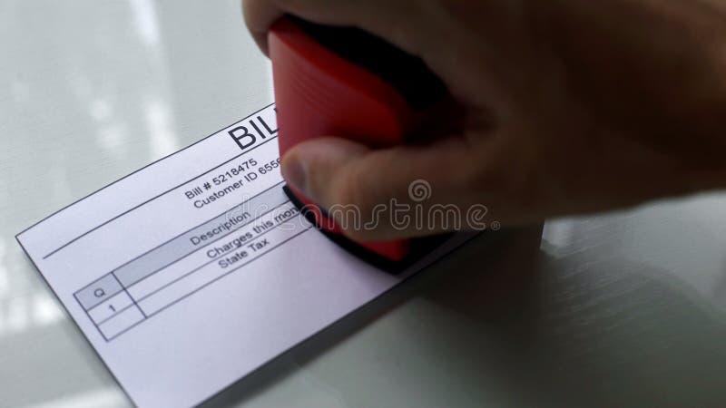 Билл, рука штемпелюя прямоугольное уплотнение на документе, оплате для обслуживаний, конце вверх стоковое фото rf