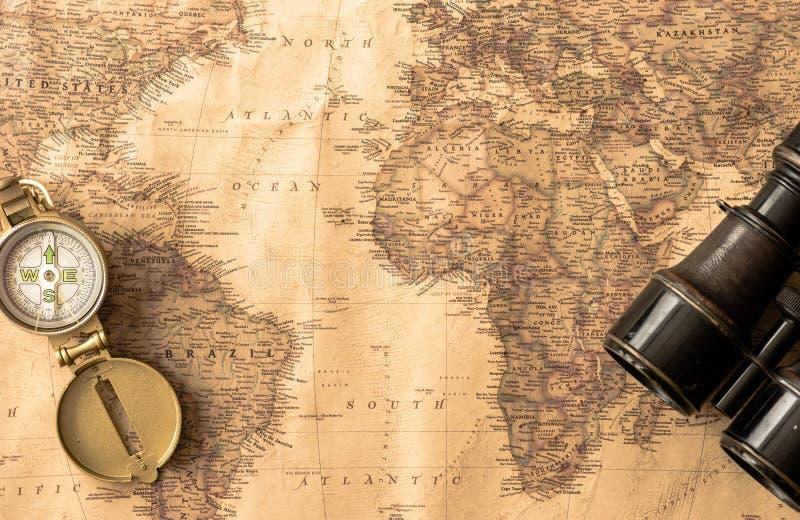 Бинокли аксессуаров перемещения, компас на старой, античной карте мира стоковые фото