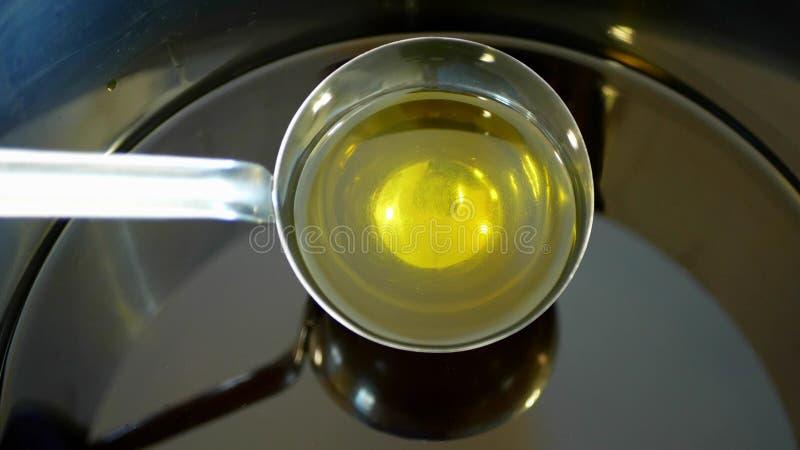 Био, жидкость оливкового масла органическое качественное полученные от оливок, пузырей активных, смешивая и лить в стальном бочон стоковое изображение