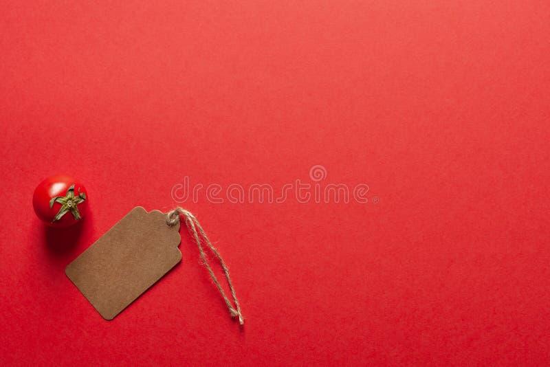 Бирка картона Kraft с веревочкой на красной предпосылке стоковое фото