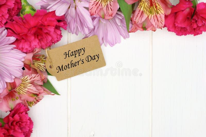 Бирка подарка Дня матери с границей угла цветка на белой древесине стоковые фотографии rf