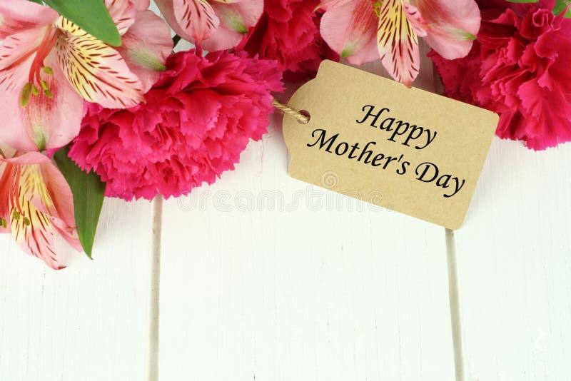 Бирка подарка Дня матери с цветками на белой древесине стоковое изображение