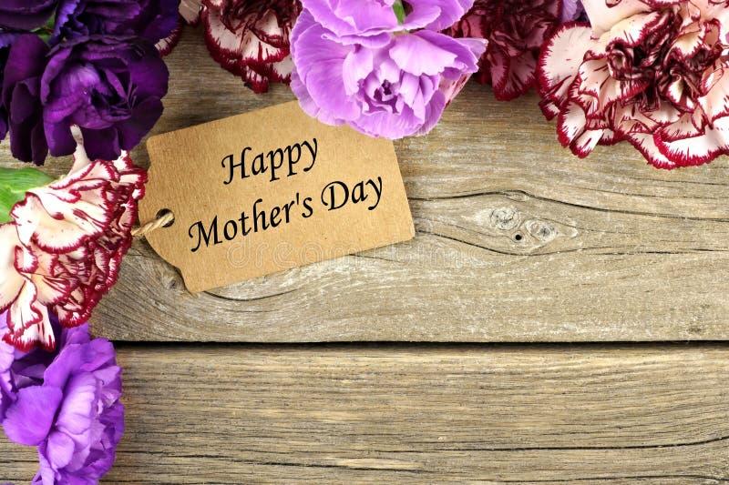 Бирка подарка дня матерей с границей угла цветка на древесине стоковые изображения