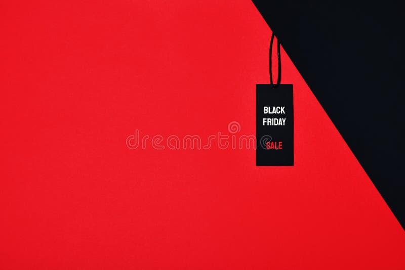Бирка продажи с черной надписью пятницы и продажи на красной и черной предпосылке стоковые фото