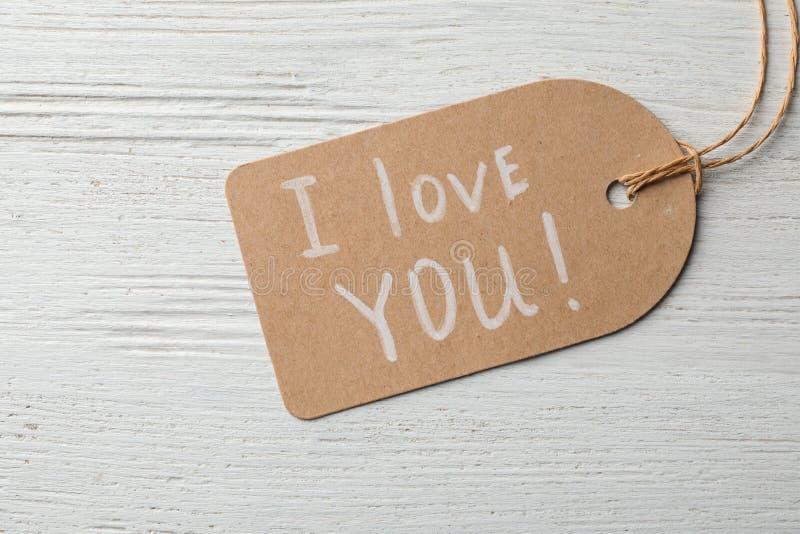 Бирка со словами Я ТЕБЯ ЛЮБЛЮ на деревянной предпосылке стоковое фото