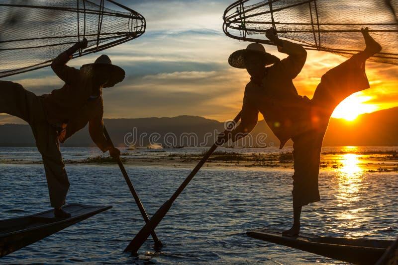 Бирманские рыбаки позируют с помощью конических сеток на закате, озеро Инле в поселке Ньяунгшве в районе Шан Хиллз Мьянмы Бирма стоковое изображение rf