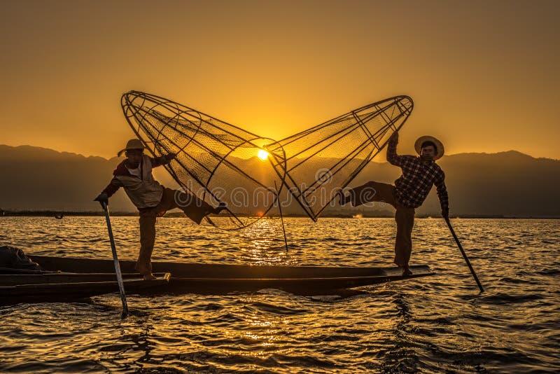 Бирманские рыболовы на бамбуковых шлюпках на восходе солнца стоковые фотографии rf