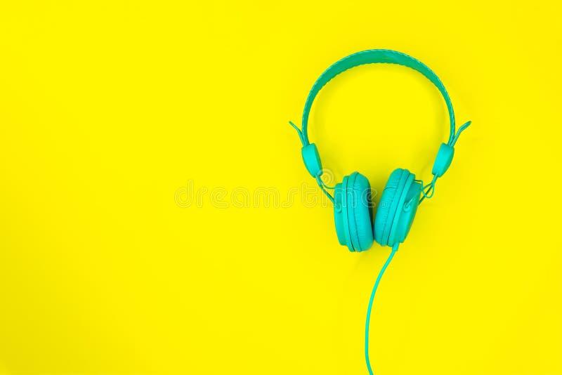 Бирюза или голубые наушники или шлемофон компьютера на желтой предпосылке с космосом экземпляра стоковое изображение