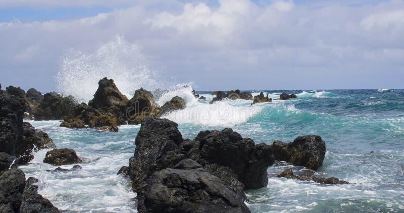 Бирюза и голубые океанские волны ломая на черной лаве стоковое фото rf