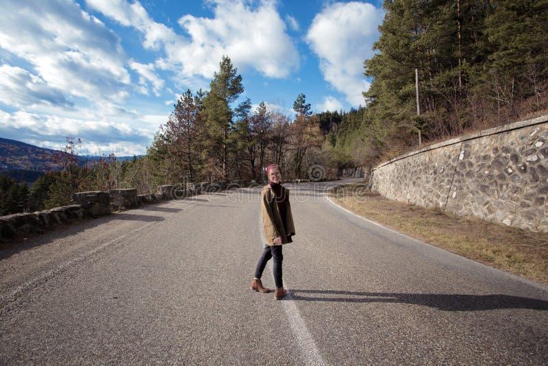 Битник девушки стоит на дороге горы стоковые фото