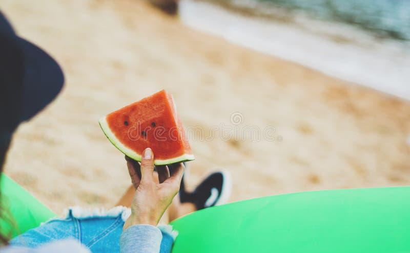 Битник маленькой девочки ослабляет на побережье и владениях пляжа в ее руке кусок красного арбуза свежих фруктов на голубой предп стоковые изображения rf