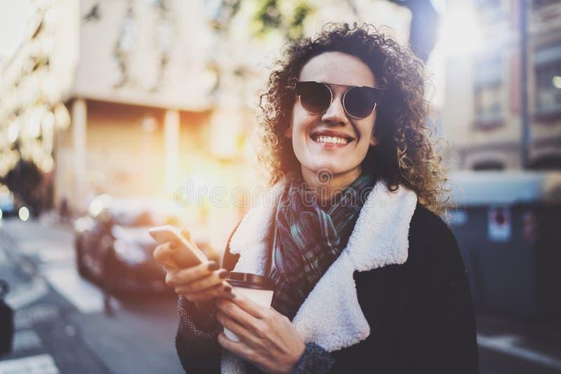 Битник молодой женщины Hansome ища информацию в передвижной сети умным телефоном, во время идти в европейский город стоковые фото