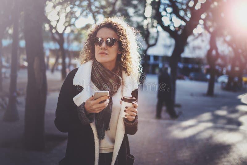 Битник молодой женщины Hansome ища информацию в передвижной сети умным телефоном, во время идти в европейский город стоковая фотография rf