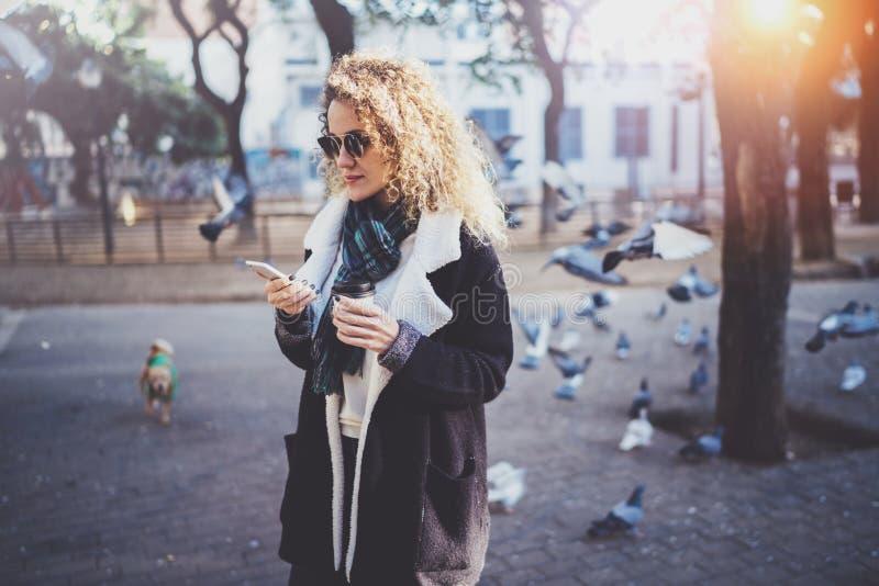 Битник молодой женщины Hansome ища информацию в передвижной сети умным телефоном, во время идти в европейский город стоковое изображение