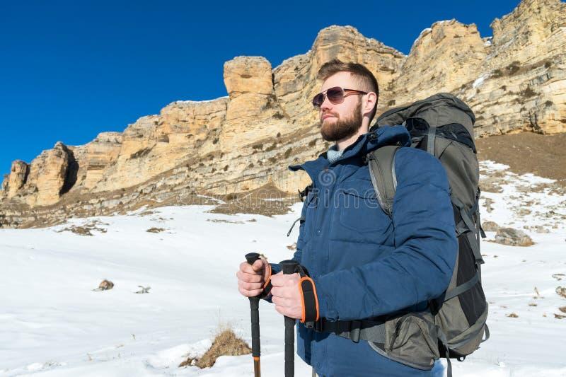 Битник портрета a бородатый с рюкзаком и в солнечных очках с большим рюкзаком на его плечах стоит с ручками стоковое изображение rf
