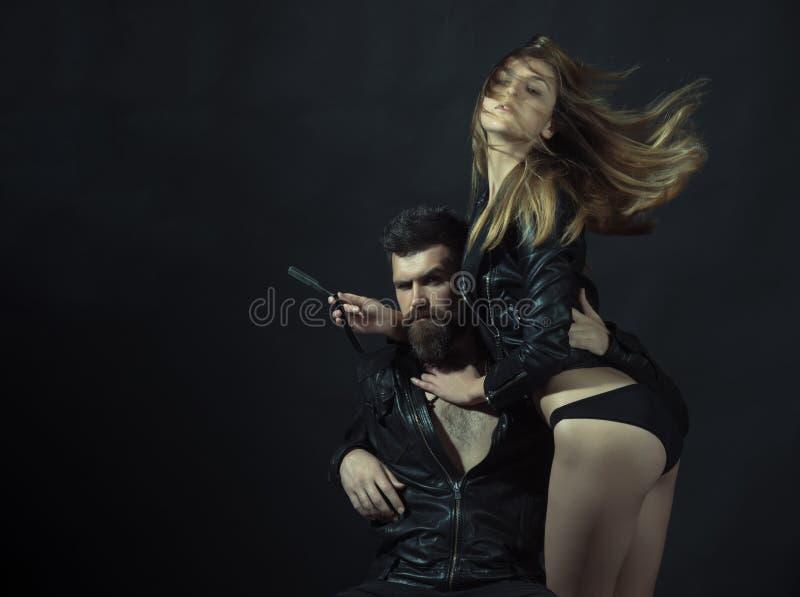 Битник с бородой и сексуальной девушкой держит прямую бритву Парикмахер с прямой бритвой работает на стрижке Пары сексуальной дев стоковое фото
