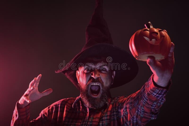 Битник хеллоуина в шляпе волшебника держа тыкву стоковое изображение