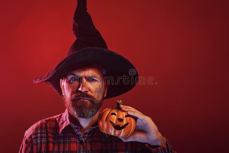 Битник хеллоуина в шляпе волшебника держа тыкву стоковые фотографии rf
