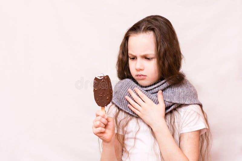 Бит девушки с мороженого и ее горла заболел стоковое фото rf