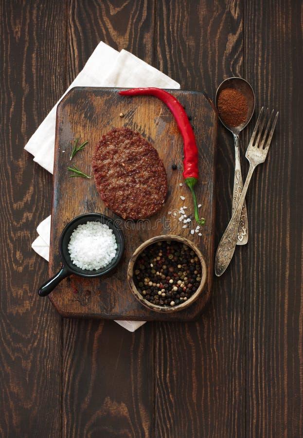 2 бифштекса, перцы и старые ложка, вилка и разделочная доска o стоковое изображение