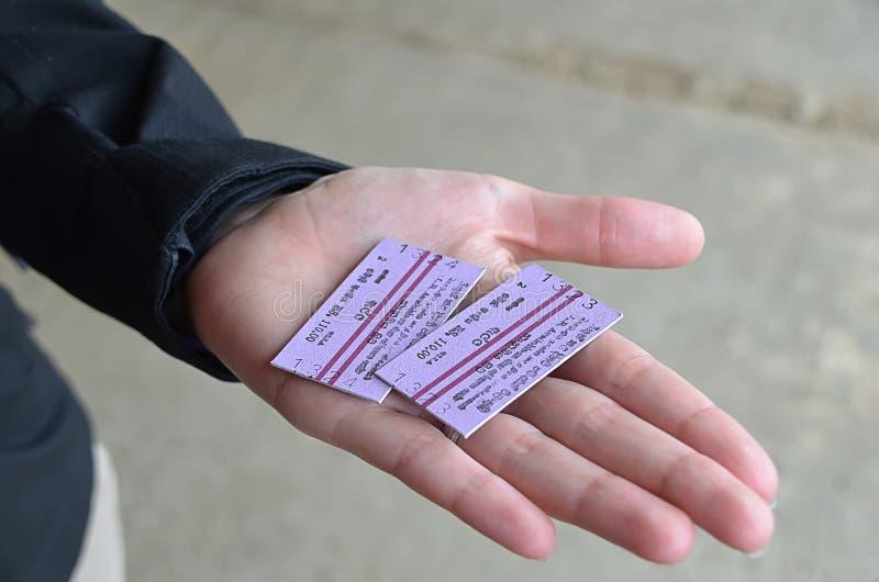 2 билета на поезд в руке девушки стоковые фото