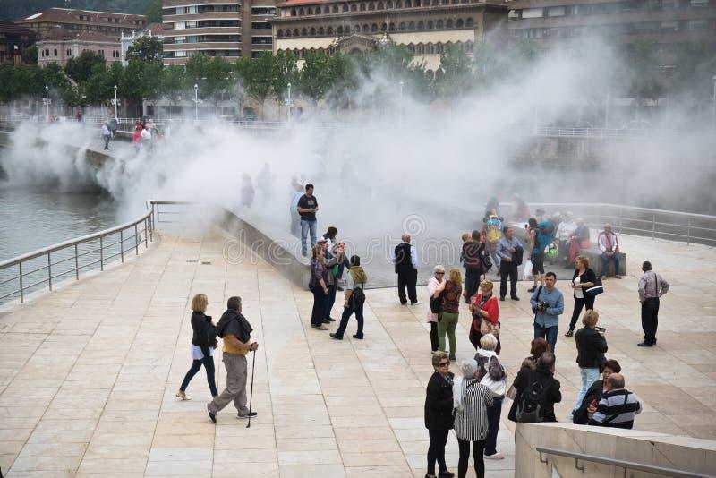 Бильбао, Испания - 17-ое мая 2017: город людей идя и sightseeing Бильбао в анимации привлекательности дыма воды guggenhe музея стоковая фотография rf