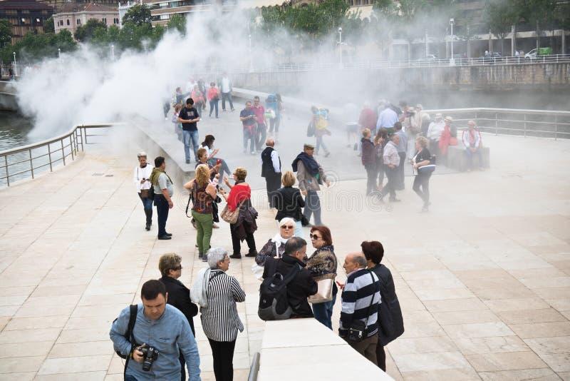 Бильбао, Испания - 17-ое мая 2017: город людей идя и sightseeing Бильбао в анимации привлекательности дыма воды guggenhe музея стоковое фото