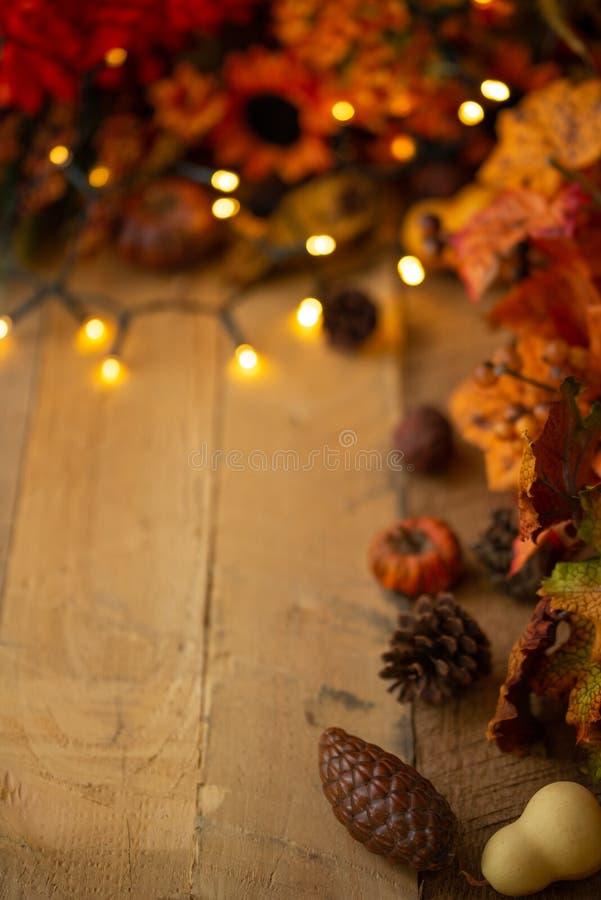 Благодарение или хеллоуин, состав осени с сухими листьями и небольшими тыквами на старом деревянном столе с накаляя светами E стоковое фото
