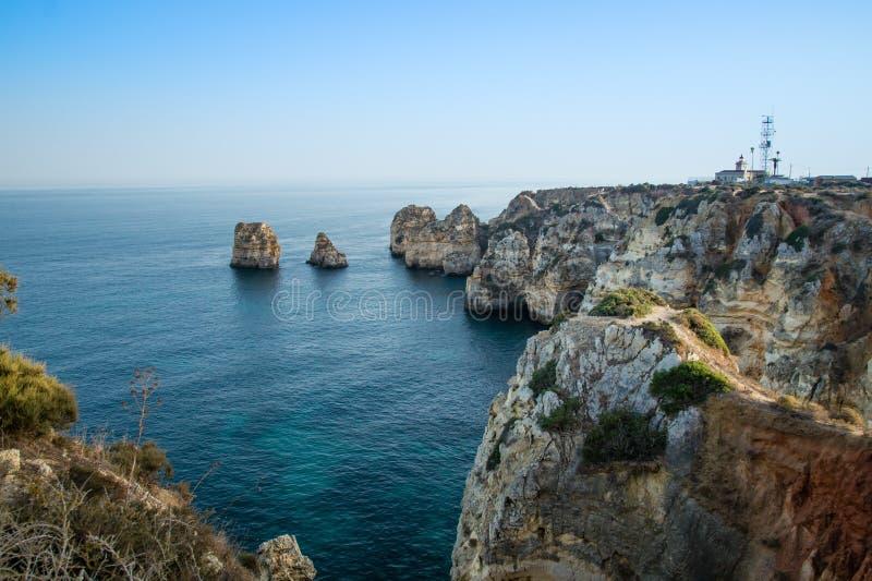 Благоустраивайте взгляд бечевника побережья Лагоса в предпосылке Farol da Ponta da Piedade, Алгарве, Португалия стоковое изображение
