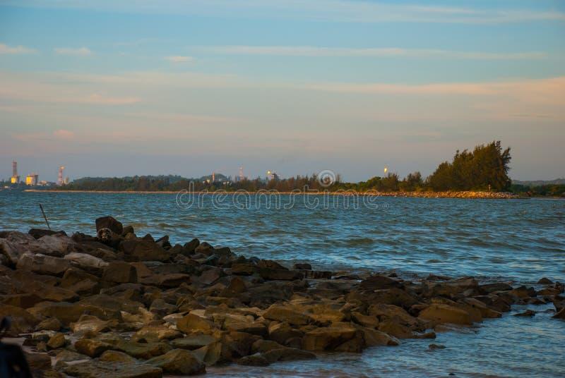 Благоустраивайте взгляд воды в трубе вечера с огнем на горизонте, городом Bintulu, Борнео, Сараваком, Малайзией Pantai Tema стоковая фотография