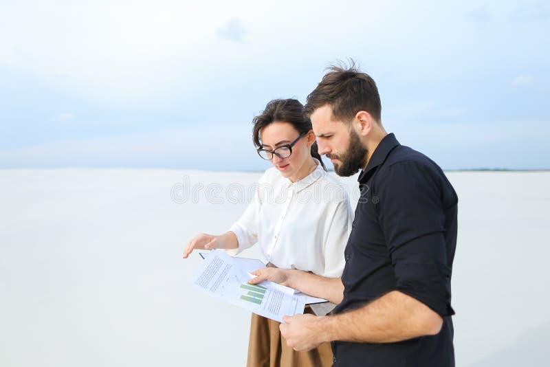 Благоустраивайте дизайнерскую женщину показывая эскизы к человеку клиента стоковое изображение rf