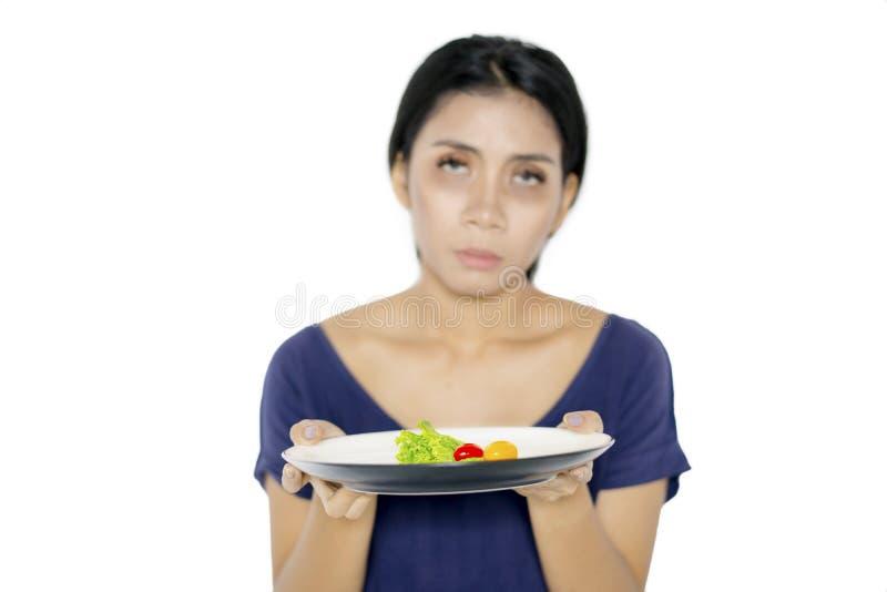 Бледная женщина держит небольшой салат части на студии стоковое изображение rf