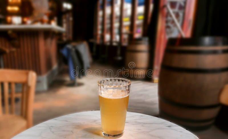 Бледный эль или пиво лагера на таблице бара Выравнивать часы досуга внутри кафа города с бочонками вина стоковое фото rf