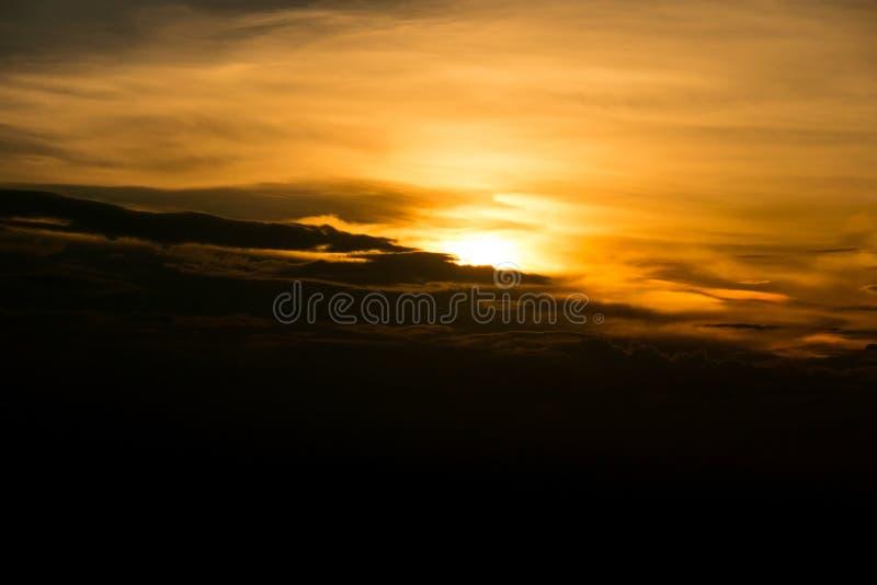 Блеск захода солнца взгляда оранжевый на небе и черной туче во времени вечера стоковая фотография