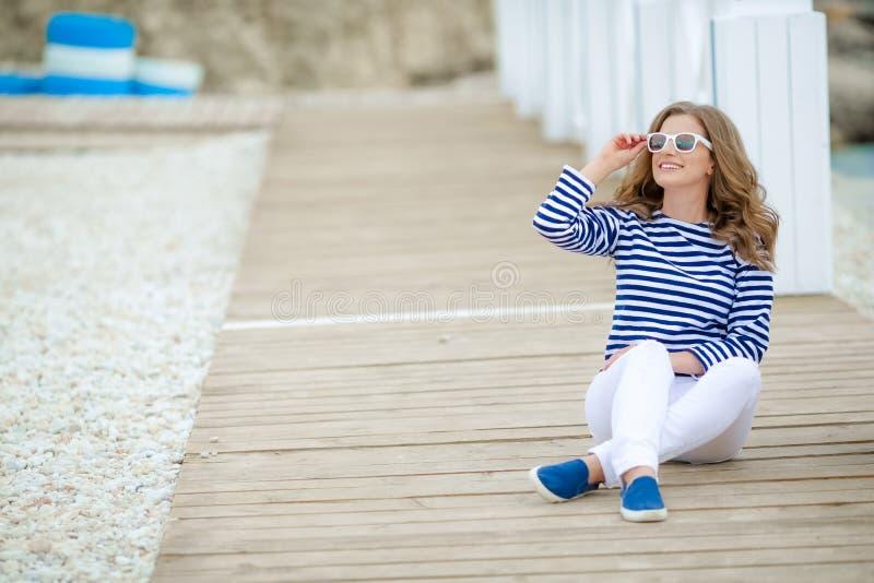 Блестящая милая молодая женщина хипстера в футболке лета белой в тапках в ультрамодных джинсах в стильных солнечных очках стоковые изображения rf