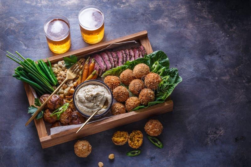 Ближневосточная еда партии: falafel, babaghanoush, картошки, говядина, зеленые veggies стоковое фото rf