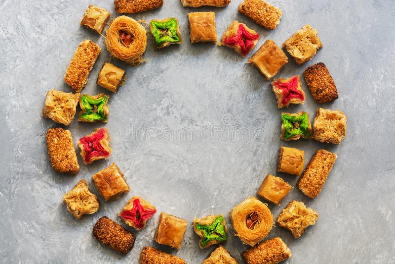 Ближневосточная традиционная бахлава десерта на серой предпосылке Круглая рамка арабских помадок над взглядом стоковые фотографии rf