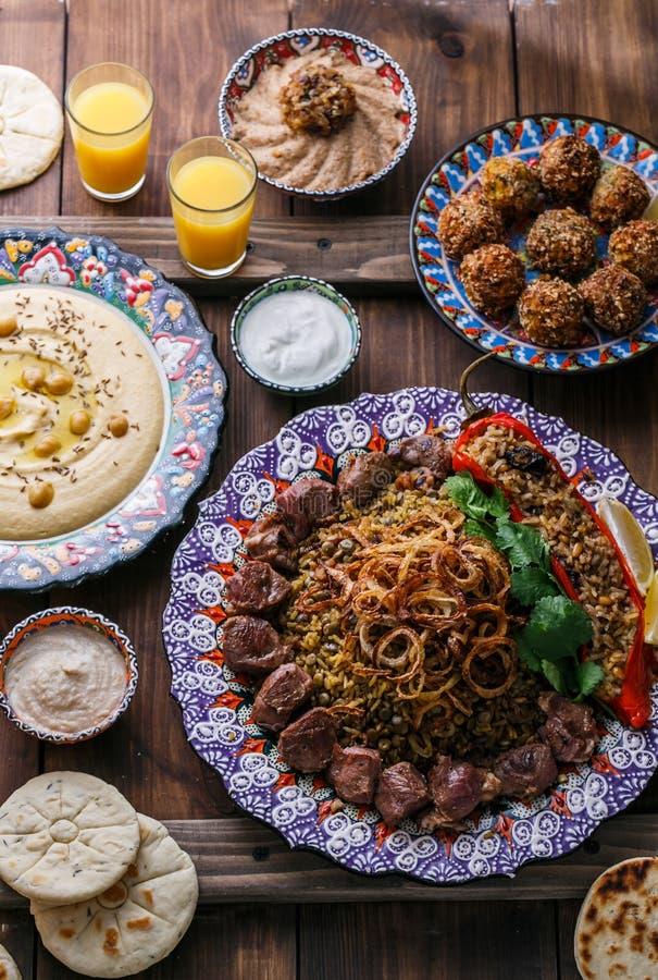 Ближневосточный или арабский pilaf с hummus, falafel, погружением баклажана и взгляд сверху пита стоковые фотографии rf