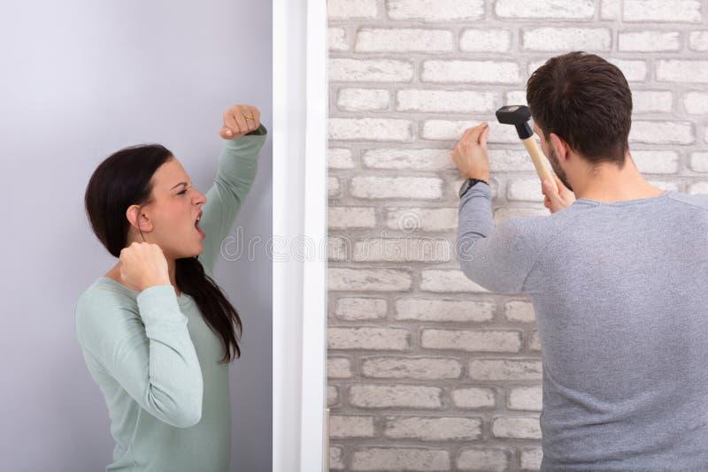Ближний ударяя ноготь на кирпичной стене с молотком стоковая фотография rf