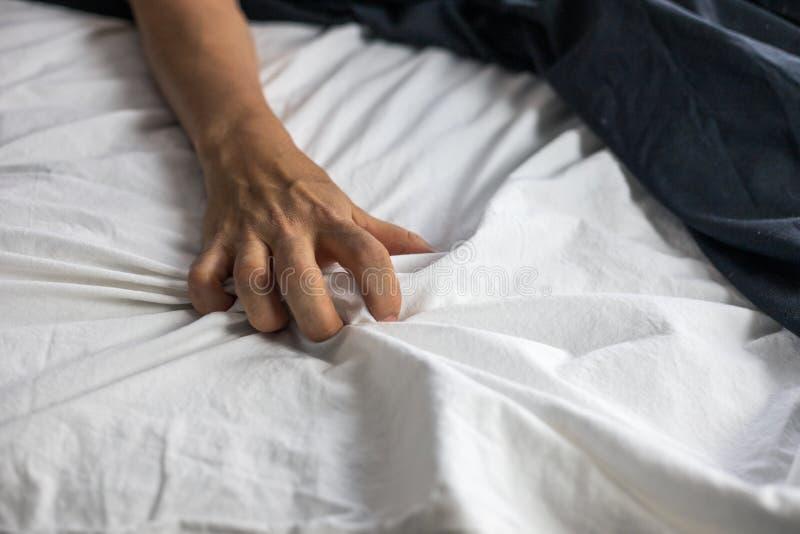 Близкая поднимающая вверх деталь руки женщин хватая дальше к простыням, интимности, эротичной концепции стоковое фото rf