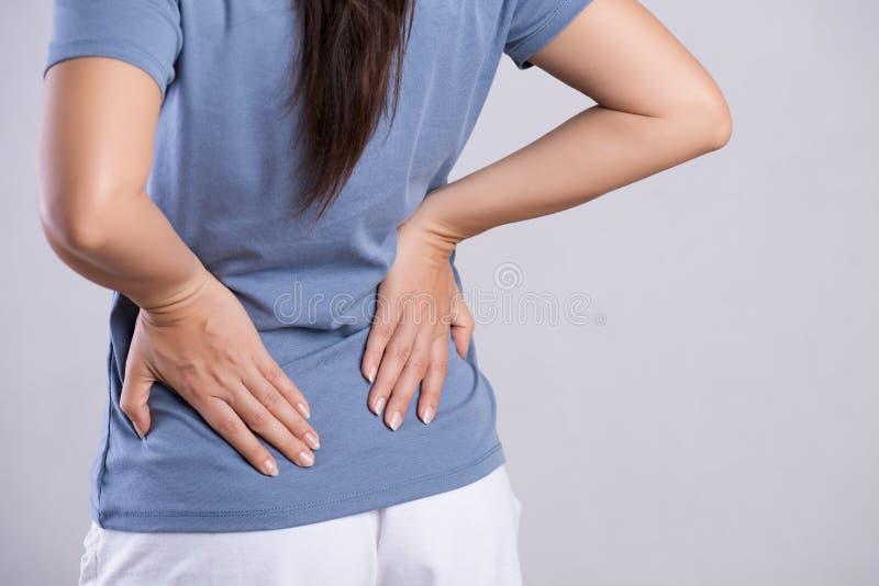 Близкая поднимающая вверх женщина имея боль в раненом назад Концепция здравоохранения и боли в спине стоковые фото
