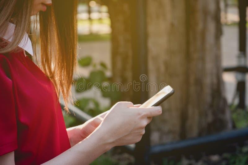 Близкая поднимающая вверх женщина используя умный телефон на парке стоковые изображения rf